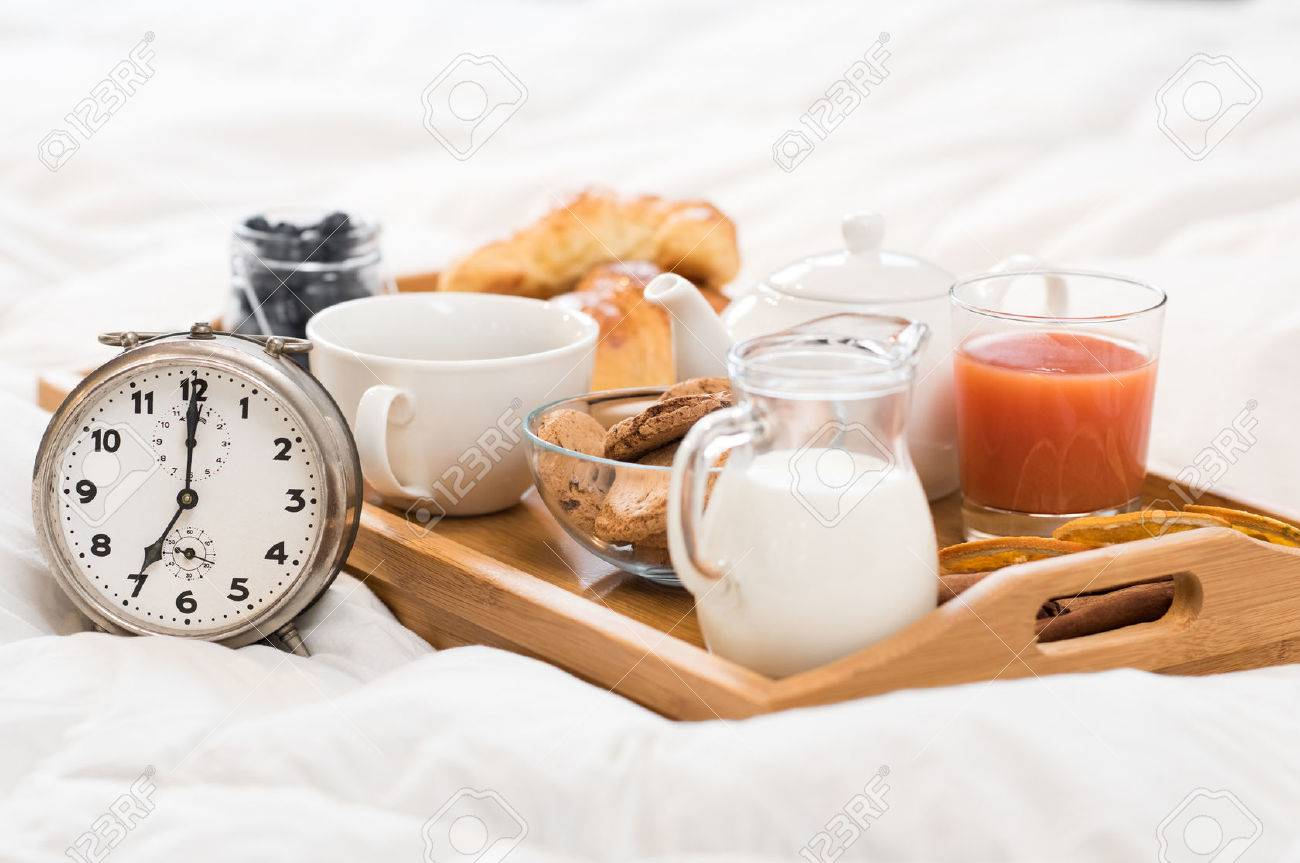 Healthy breakfast served on a tray on bed with alarm clock. Banque d'images - 53544909