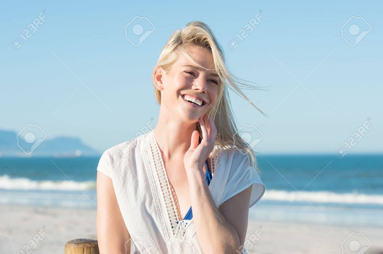 Portrait of happy smiling woman on the beach. Smiling sensual blonde posing on a beautiful wild beach. Pretty girl in casaul looking away and laughing. - 54852299