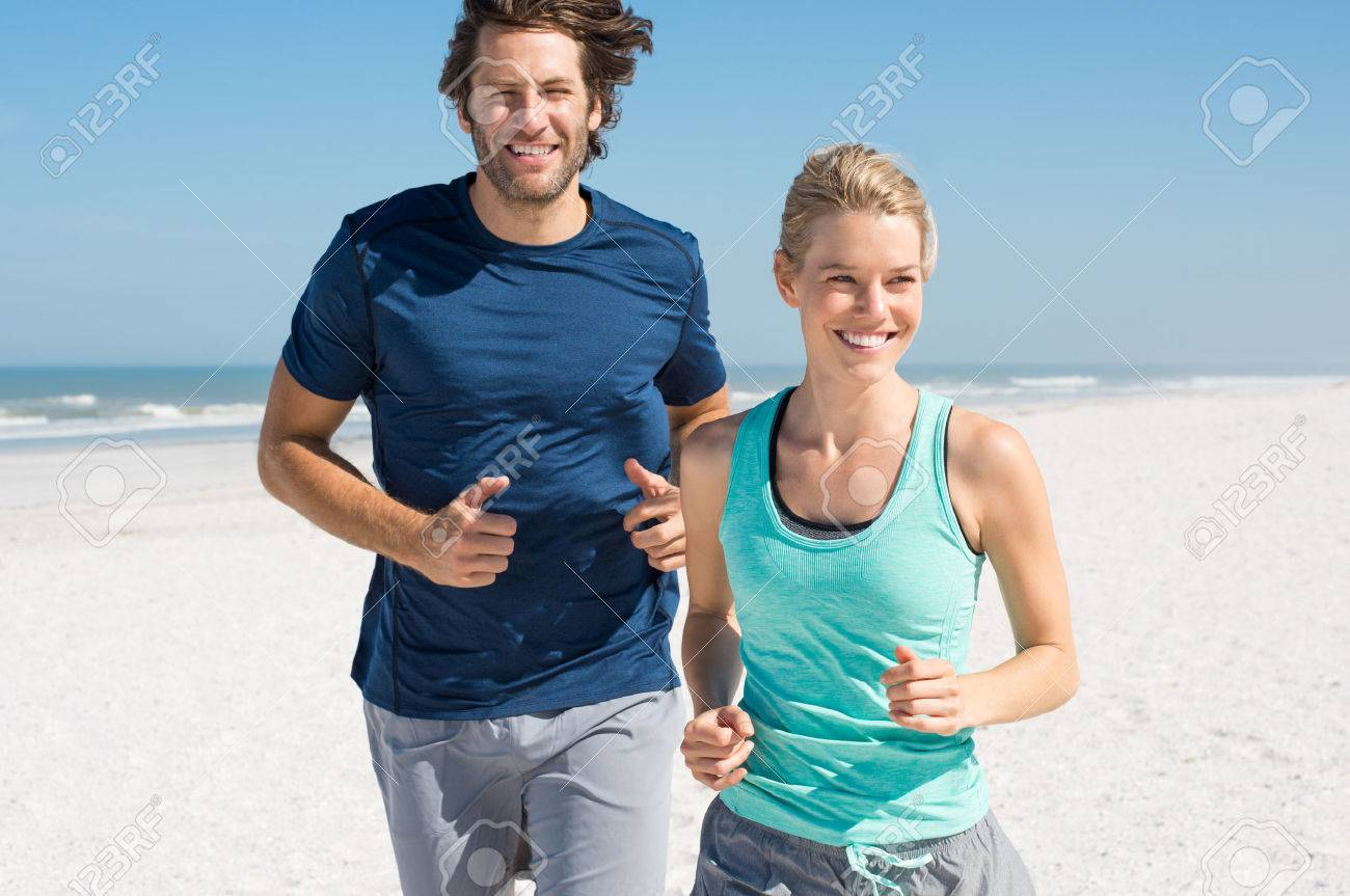 Couple exercising at beach. Trainer training athlete for fitness. Athletics jogging in summer sport shorts enjoying the sun. Banque d'images - 54852310