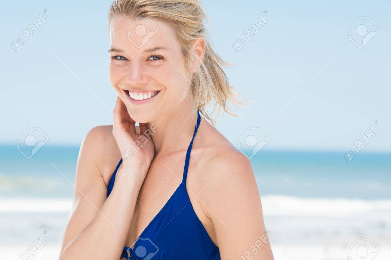 Portrait of attractive woman standing at beach. Happy smiling girl looking at camera at seaside. Young blonde woman relaxing at beach. - 54852386