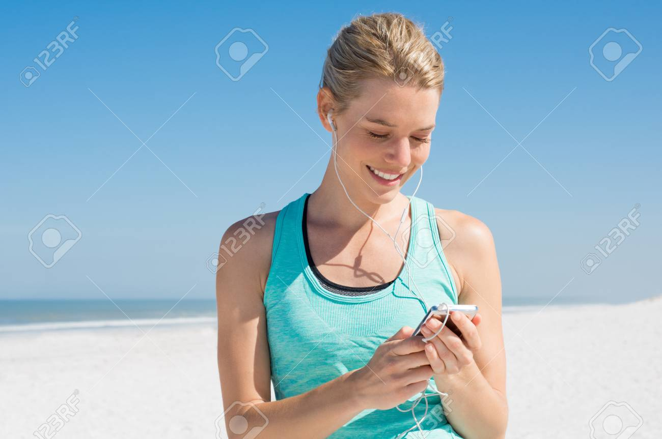Young woman listening to music during workout  Runner woman checking