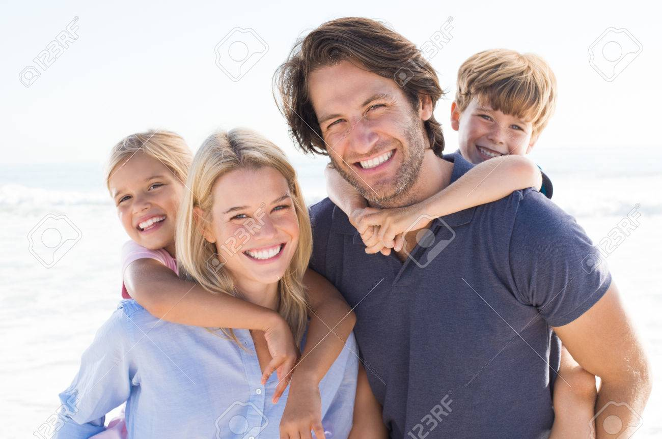 Parents giving piggyback ride to kids at beach. Close up of smiling family having fun at summer vacation. Portrait of happy family looking at camera at beach. - 54852670