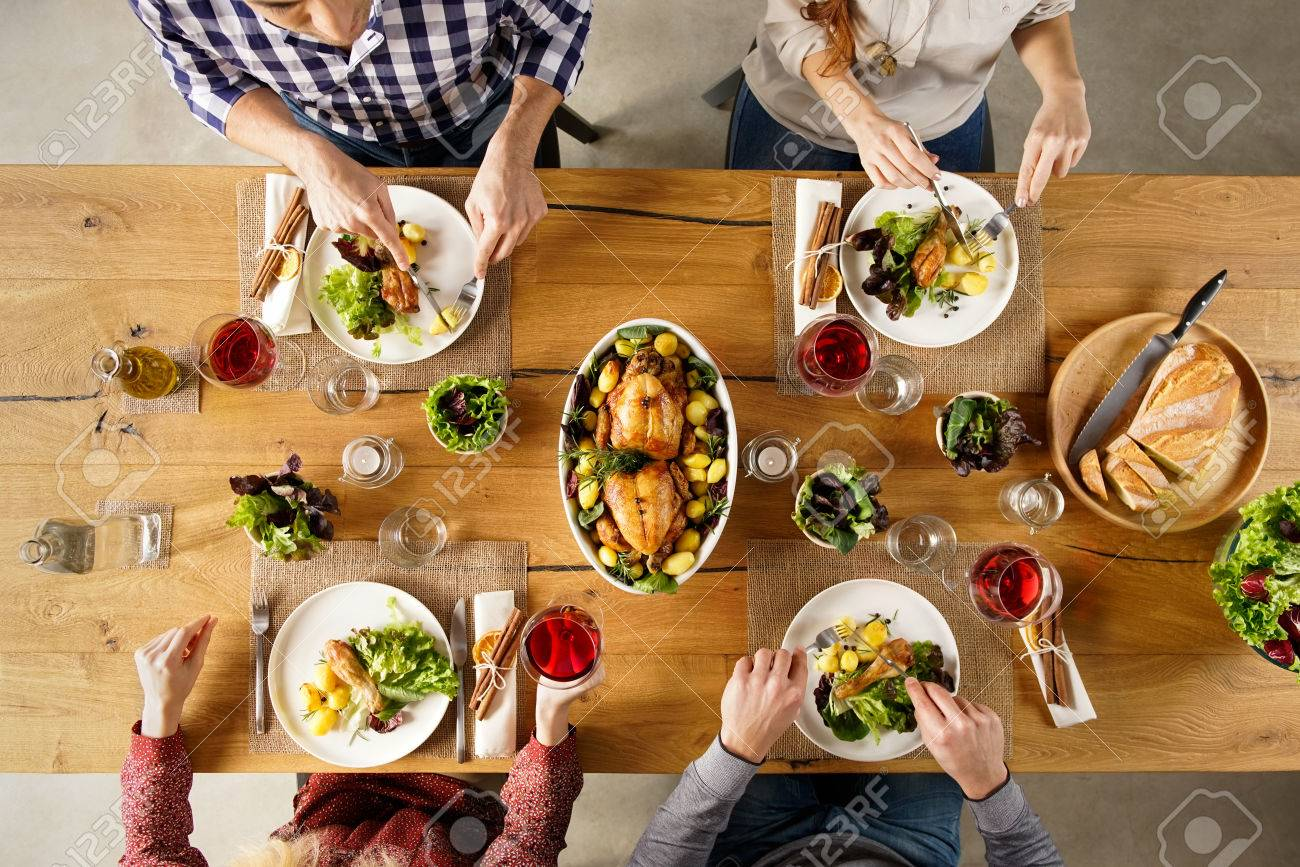 Dinner table top view - Stock Photo Top View Of Dining Table With Salad And Roasted Chicken With Potatoes High Angle View Of Happy Young Friends Having Lunch At Home