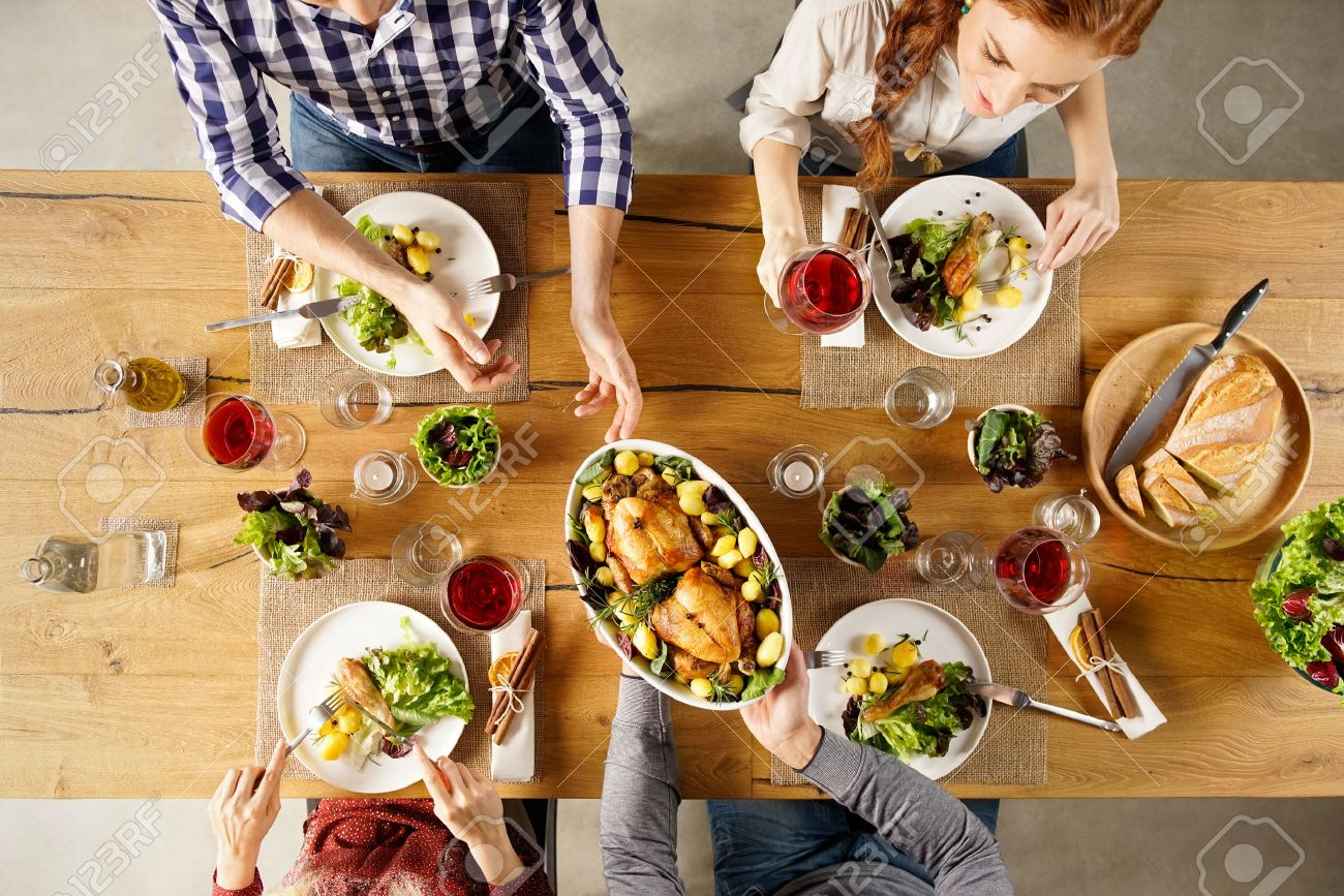 Top view of man passing food bowl to friend. High angle view of happy young friends eating together at home. Happy men and women having lunch with roasted chicken. Banque d'images - 56370745