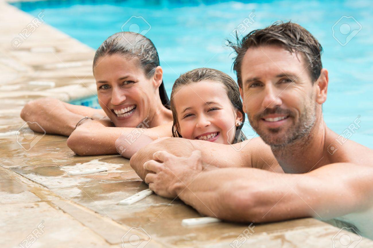 Jolie petite fille avec ses parents dans la piscine. Happy family souriant et en regardant la caméra dans la piscine. Portrait d'un couple heureux avec sa fille dans la piscine. Banque d'images - 56370753