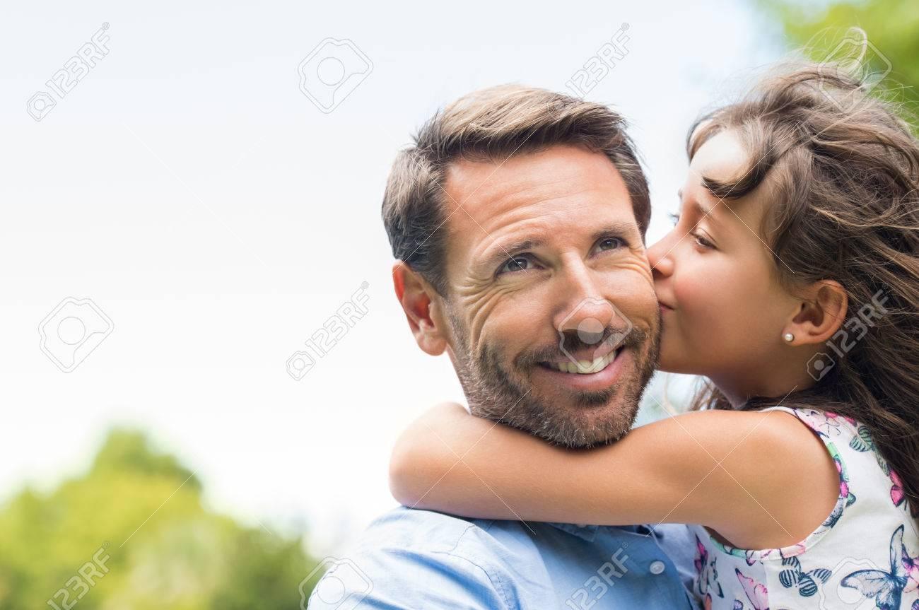Portrait d'une petite fille embrassant son père sur la joue. Jolie fille donnant un baiser à son père en plein air. Aimer étreinte de l'enfant et en embrassant son père. Banque d'images - 56370715