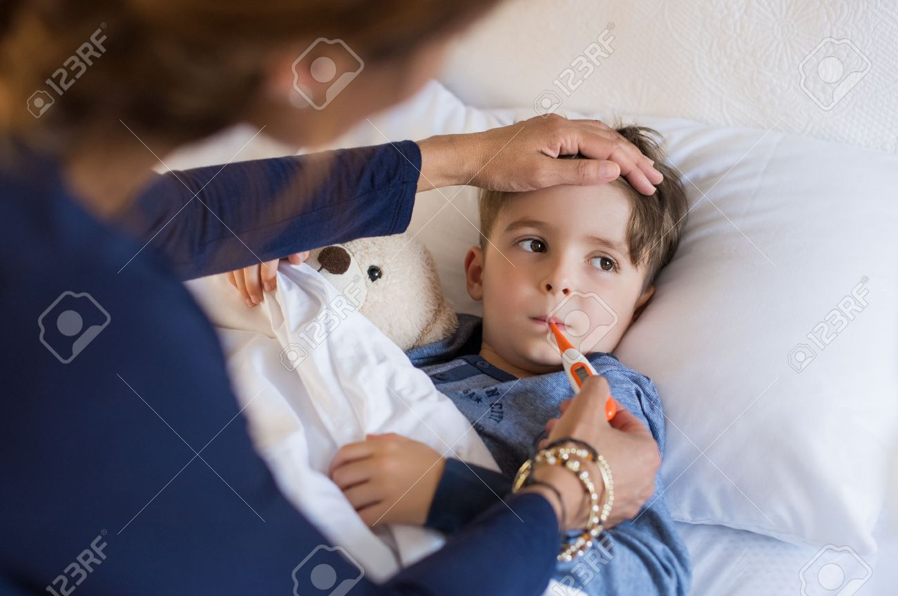 Sick boy with thermometer laying in bed and mother hand taking temperature. Mother checking temperature of her sick son who has thermometer in his mouth. Sick child with fever and illness while resting in bed. - 56370716