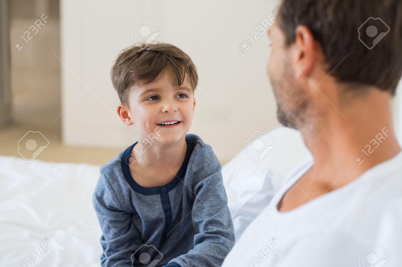 3e6faefe2 Padre E Hijo Sentado En La Cama Y Hablando Entre Sí. Padre Y Sonriente Niño  Pequeño Jugando Mientras Estaba Sentado En La Cama.