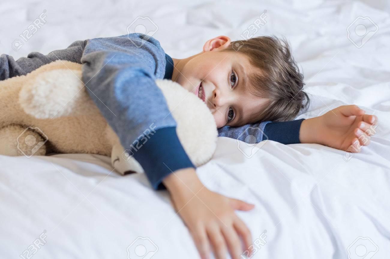 Jeune garçon se réveiller le matin avec ours en peluche. Heureux petit garçon mignon sensation de fraîcheur après une bonne nuit de sommeil. Sourire