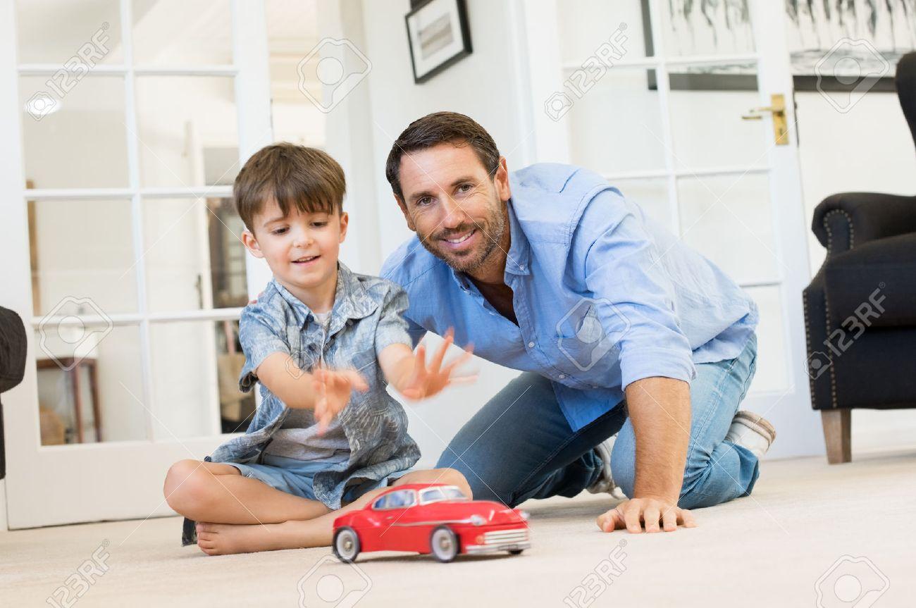 Père avec petit garçon jouant avec la voiture de jouet. père en souriant et son fils heureux de jouer ensemble dans le salon. Père de passer du temps de qualité avec son fils à la maison. Banque d'images - 56370691
