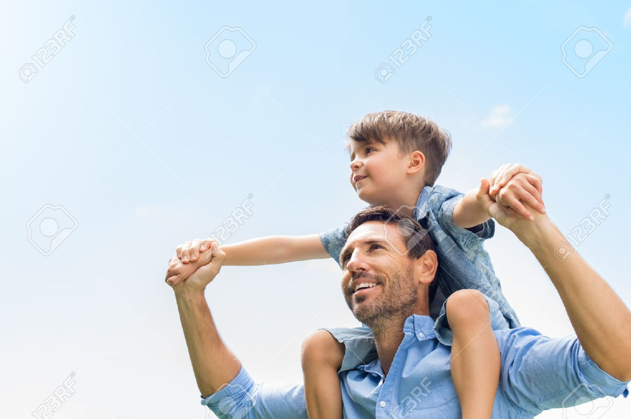 Father giving son ride on back in park. Portrait of happy father giving son piggyback ride on his shoulders and looking up. Cute boy with dad playing outdoor. Banque d'images - 56370622