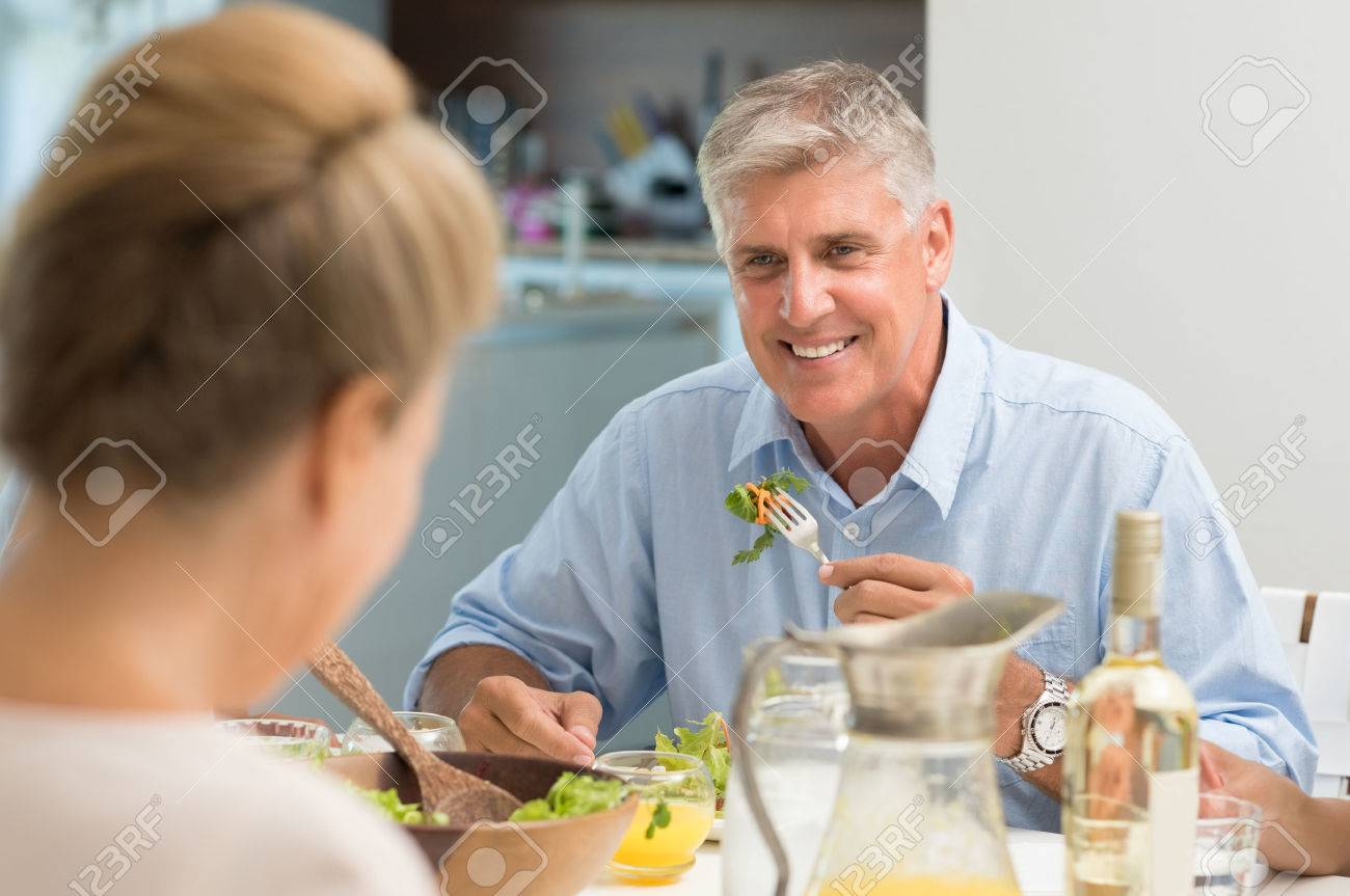 Portrait of senior man eating food while looking at wife. Healthy older man having lunch at home. Cheerful couple enjoying lunch. - 56370581