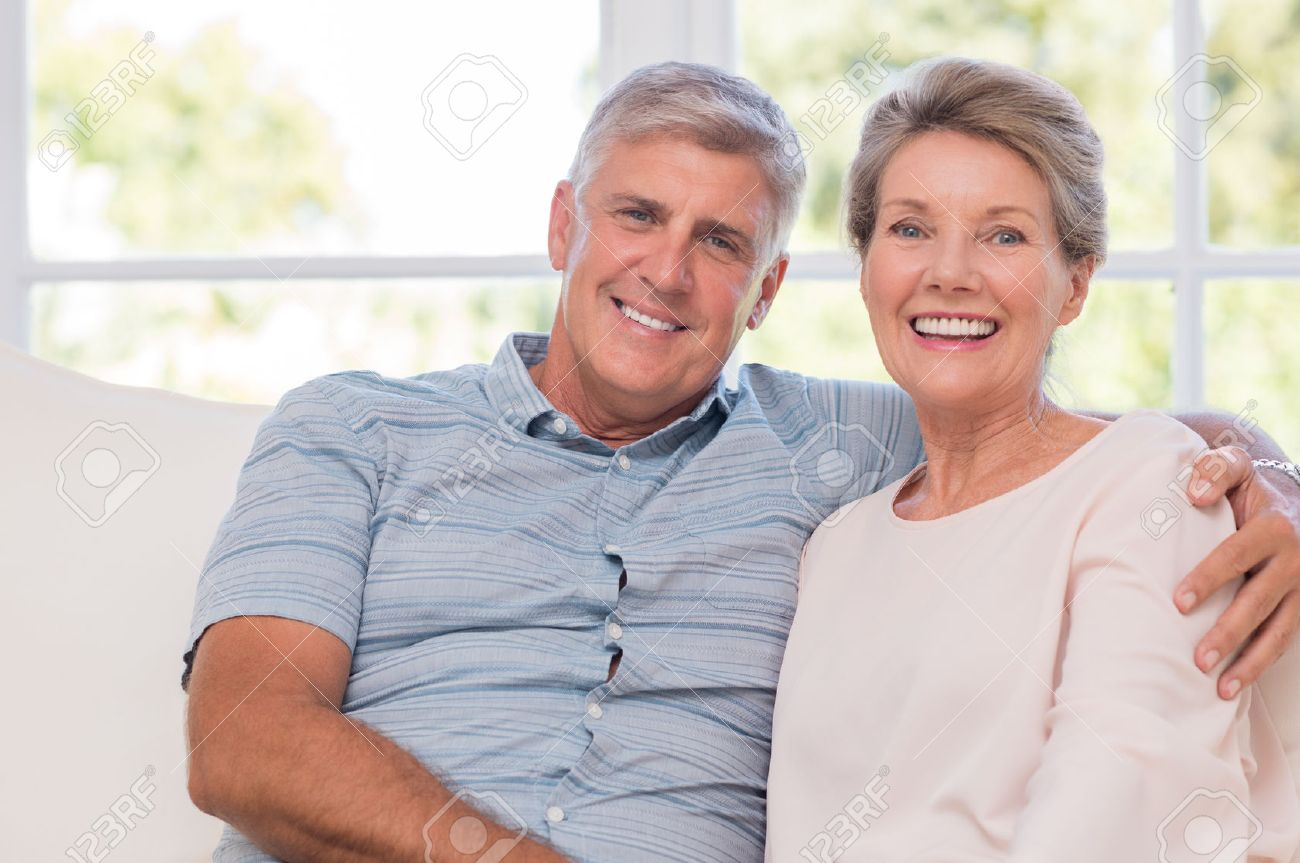 Smiling senior woman, and man sitting together on a sofa. Portrait of a candid older couple enjoying their retirement at home. Happy smiling senior couple embracing together and looking at camera. Banque d'images - 56370569