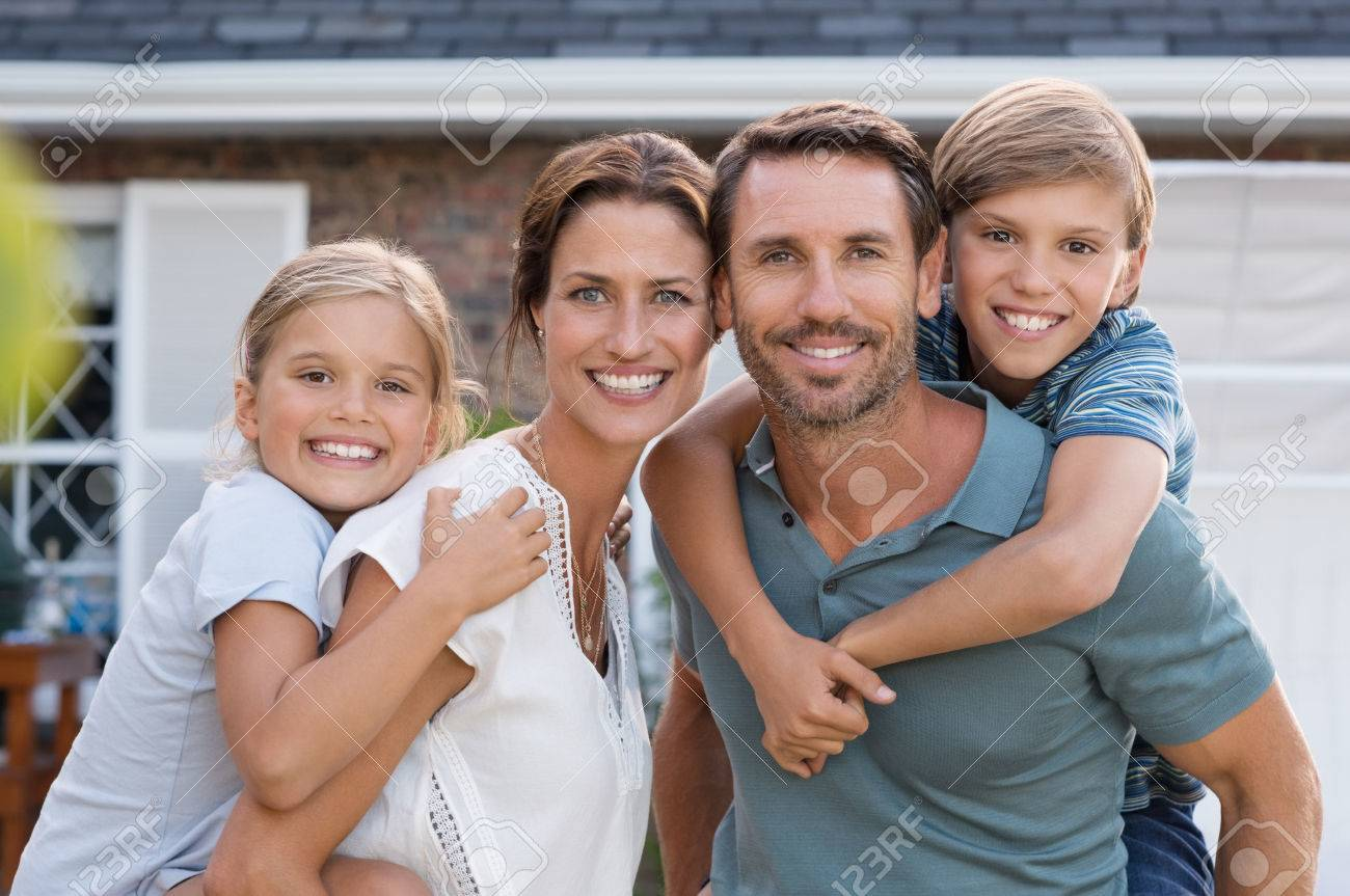 Parents giving piggyback ride to children. Happy mother and father with son and daughter looking at camera outside house. Portrait of happy couple standing carrying on shoulder their children. - 56370547