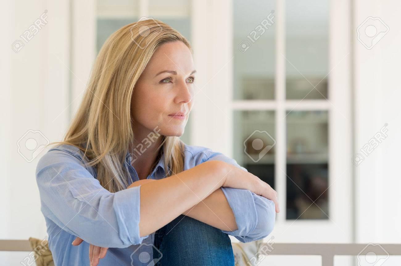 Femme assise en dehors de la maison et penser à sa nouvelle idée. Pensive femme mi détente à la maison un jour férié. Portrait de femme mûre à planifier son avenir. Banque d'images - 56766133