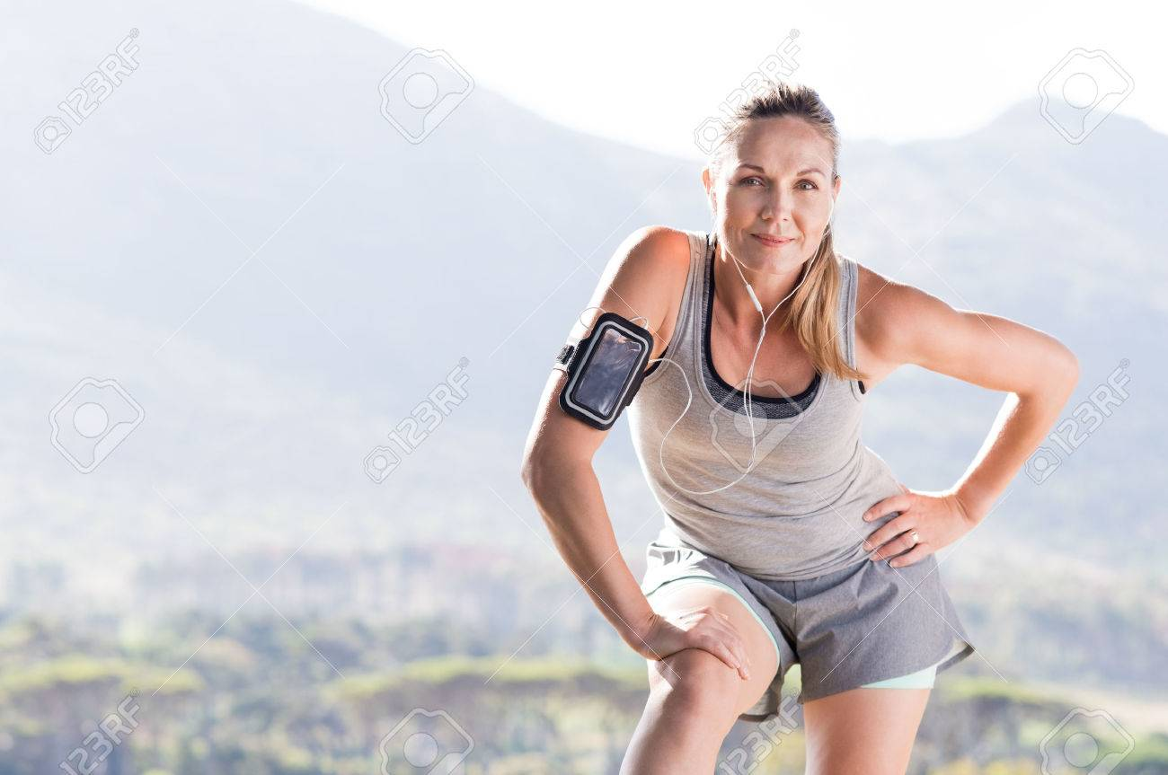 Senior female jogger resting after running in a park. Proud mature woman stretching in the park and looking at camera. Senior active woman completing her daily routine workout. - 56766150