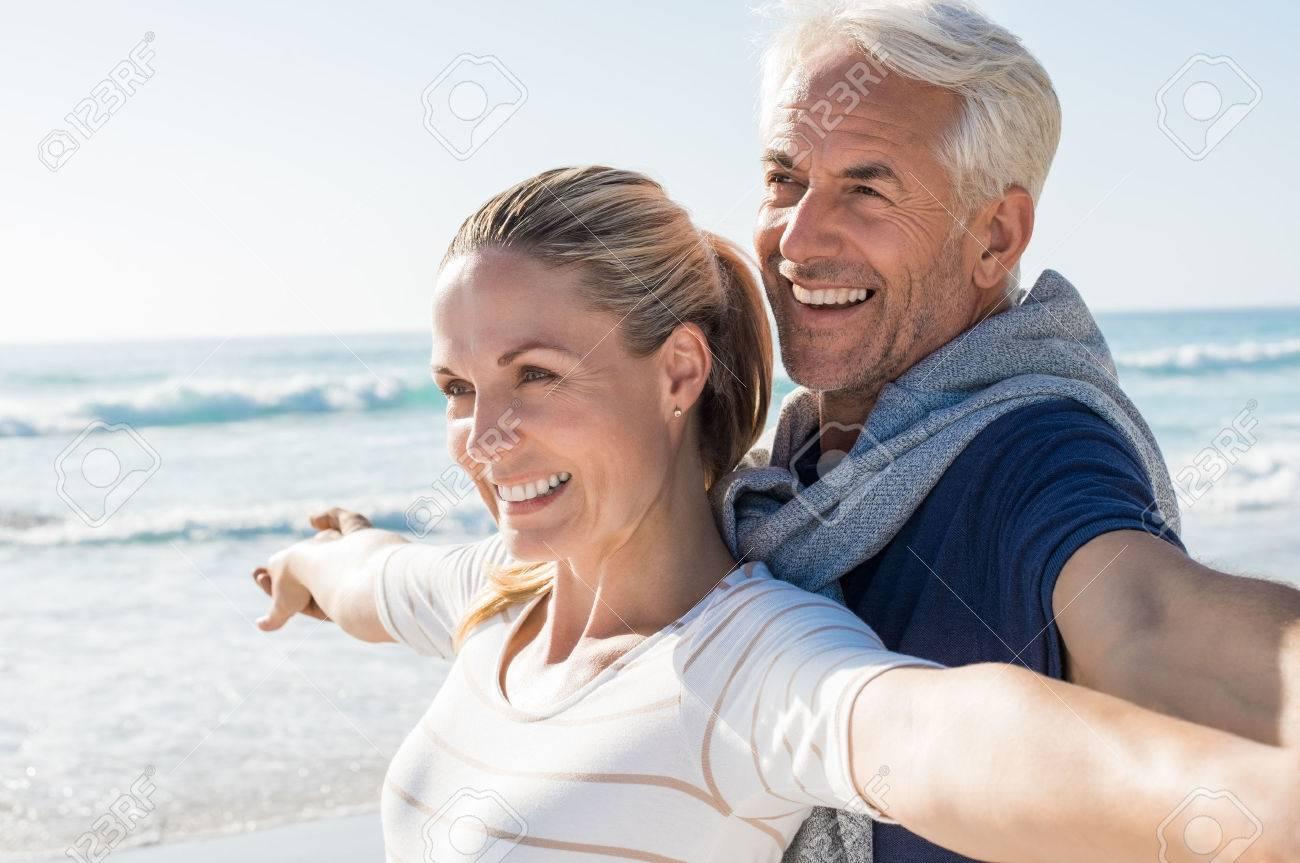 Heureux couple de personnes âgées debout sur la plage avec les bras tendus et regarder ailleurs. Couple heureux à la plage sur une journée ensoleillée. mari retraité et femme souriante à penser à leur avenir. Banque d'images - 56766168