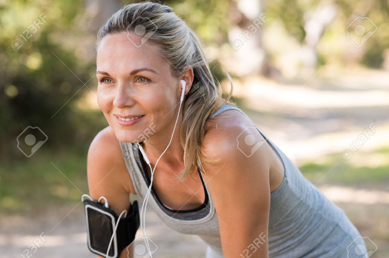 Portrait of athletic mature woman resting after jogging. Beautiful senior blonde woman running at the park on a sunny day. Female runner listening to music while jogging. Banque d'images - 56766196