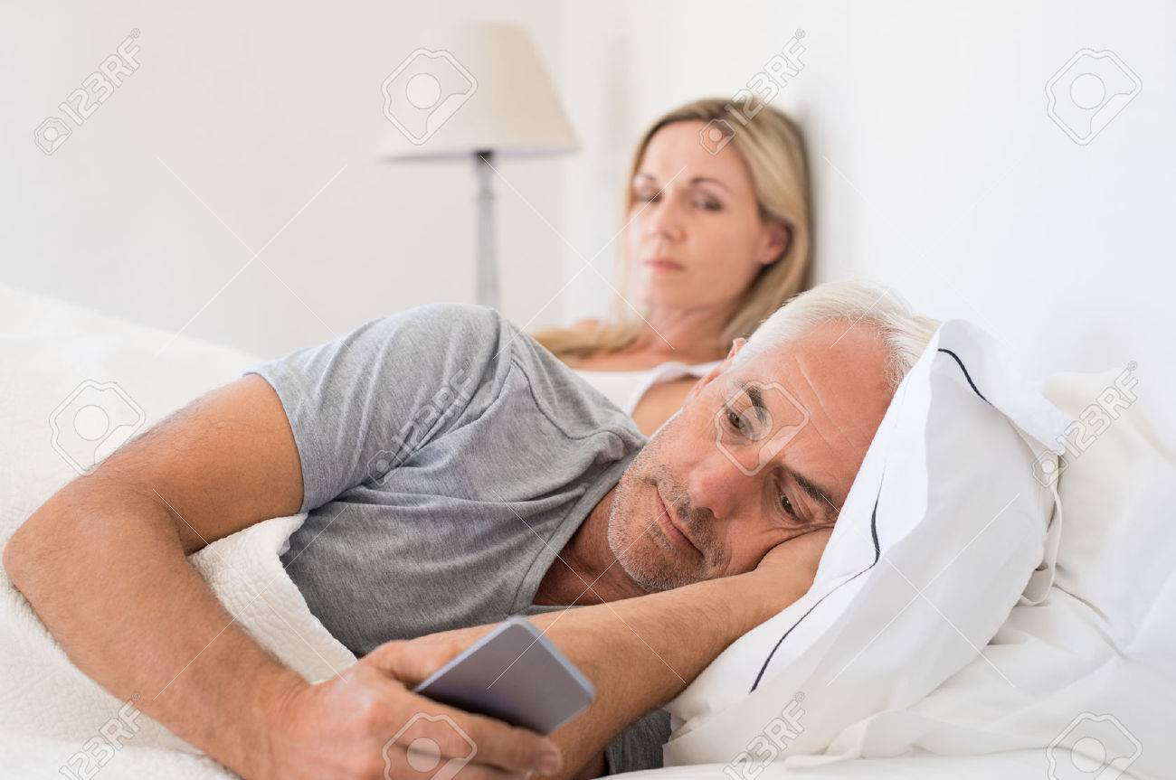 Jealous woman spying her husband mobile phone while he is reading a message. Senior couple in bed while wife is angry as husband using smartphone. Senior husband ignoring wife and texting on smartphone. Banque d'images - 56766210