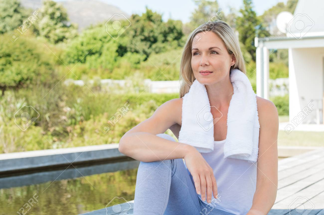relaxed woman sitting in balcony after exercising. mature woman