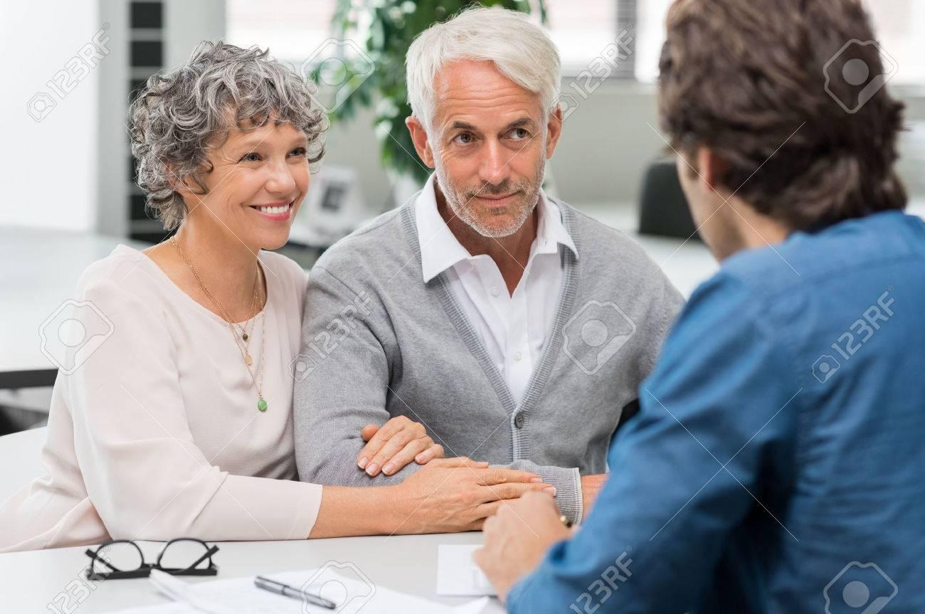Troisième réunion de l'agent immobilier de couple. conseiller financier principal couple réunion pour l'investissement. Heureux homme mûr et femme écoutant de plans Vaus d'investissement pour leur retraite. Banque d'images - 58367023