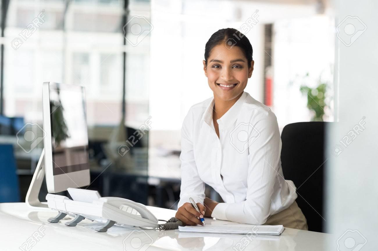 Portrait de la belle jeune femme d affaires assis à son bureau