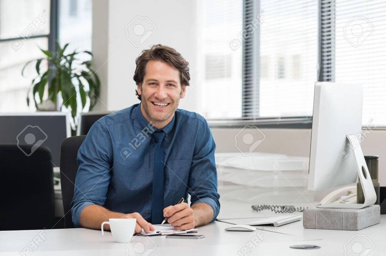 Freundlicher Junger Geschaftsmann Am Schreibtisch Im Buro Arbeiten