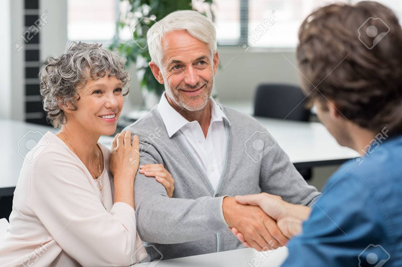 Happy senior couple shaking hands with retirement consultant. Smiling senior man shaking hands with young businessman for business agreement. Handshake between senior man and financial agent after obtaining a loan. Banque d'images - 58367031