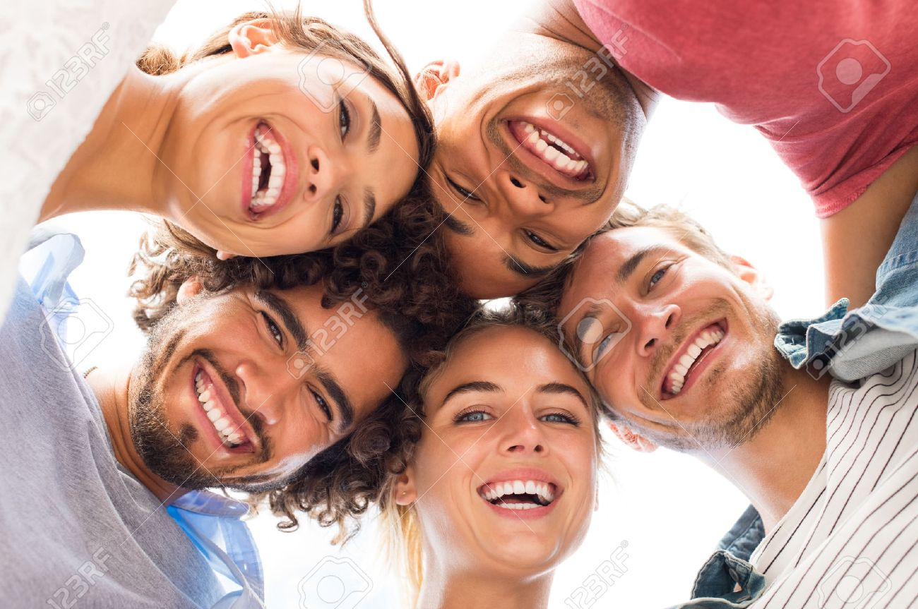Directly below shot of young friends forming huddle. Low angle view of girls and guys with their head forming a circle. Portrait of young people looking at camera. Friendship and unity concept. - 59968115