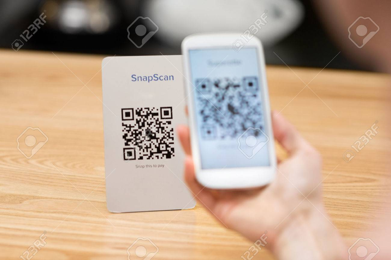 Closeup of a hand holding phone and scanning qr code. Woman hand paying with qr code. Close up of customer hand making payment through smart phone and scan code. Banque d'images - 59968168