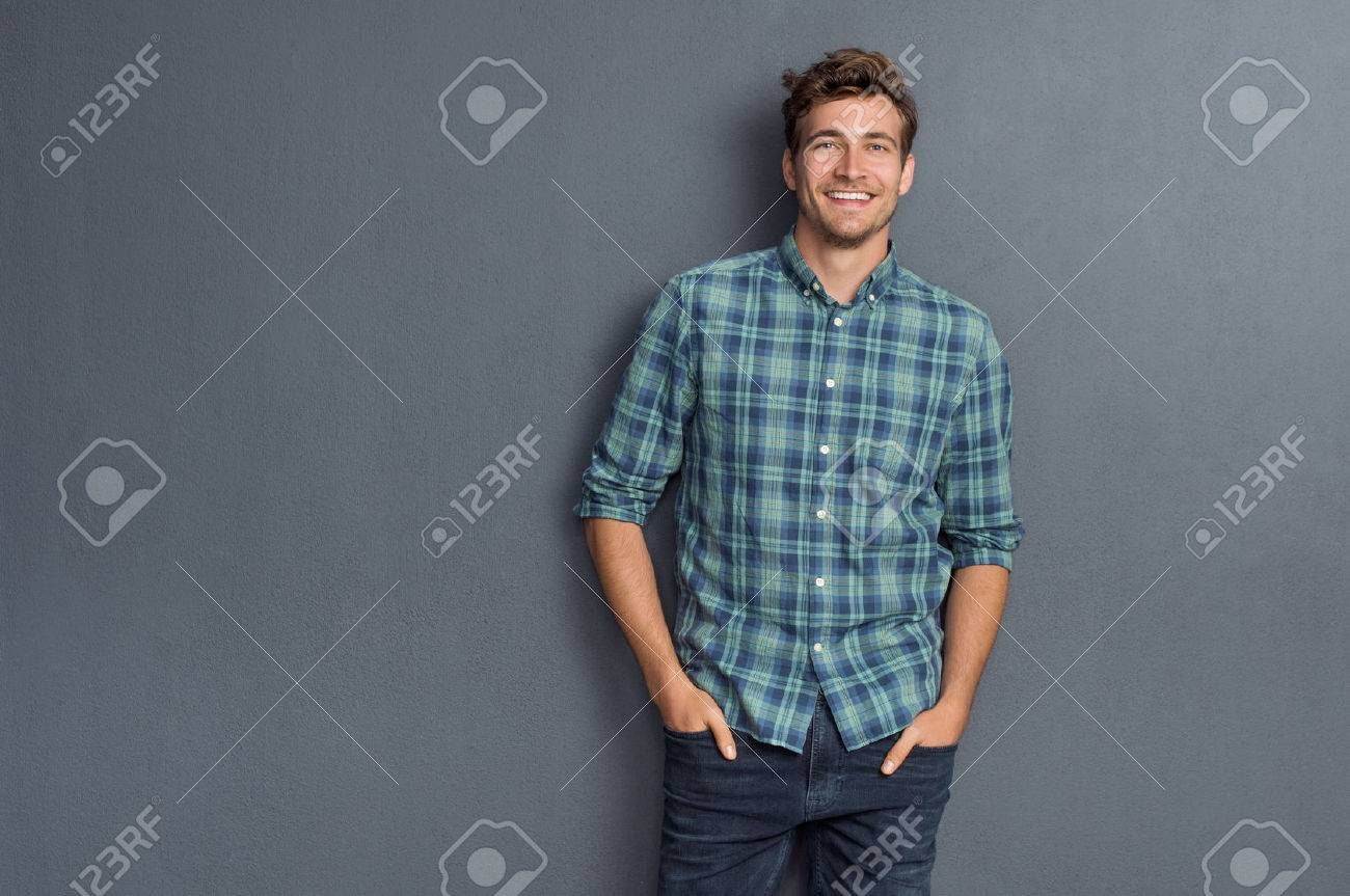 Handsome young man on grey background looking at camera. Portrait of laughing young man with hands in pockets leaning against grey wall. Happy guy smiling. - 61412434
