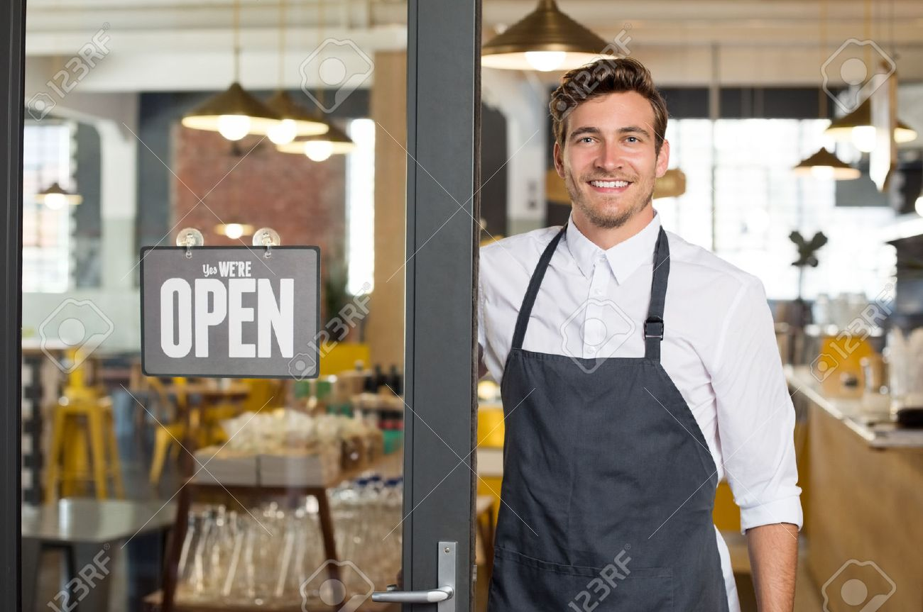 Portrait of smiling owner standing at his restaurant gate with open signboard. Young entrepreneur leaning at the cafeteria door and looking at camera. Chef or waiter standing in front of coffee shop. - 59968227