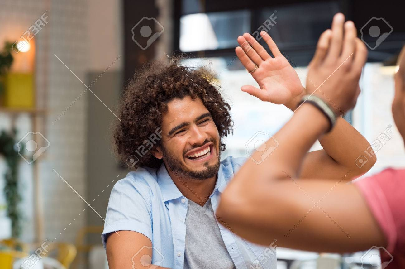 Portrait of friends giving high five at cafe while having lunch. Young guys friends giving a high five, slapping each others hand in congratulations while sitting in cafeteria. Banque d'images - 59968237