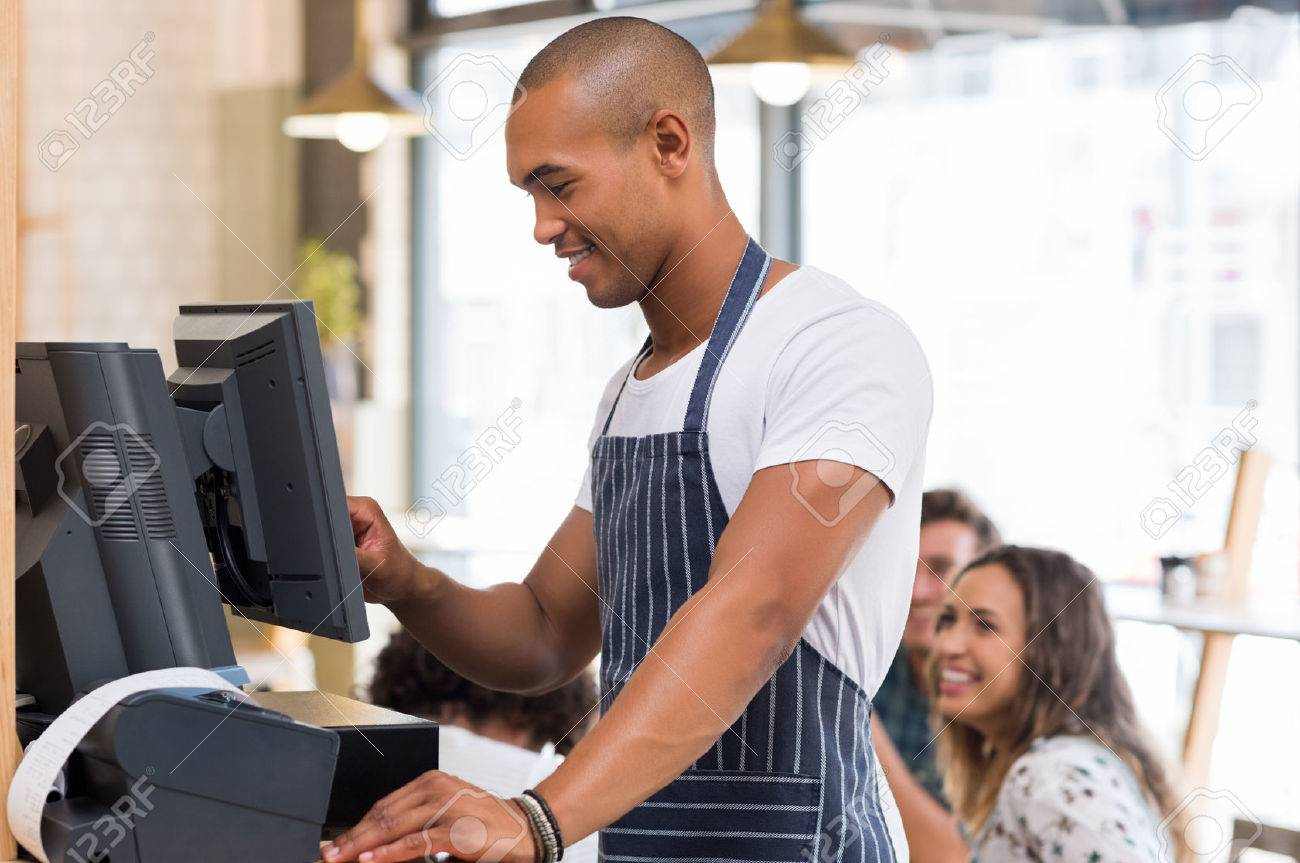 Happy young waiter in blue apron checking bill before printing it. Young african waiter printing bill in cafeteria. Waiter printing order on digital cash register. Banque d'images - 59968264
