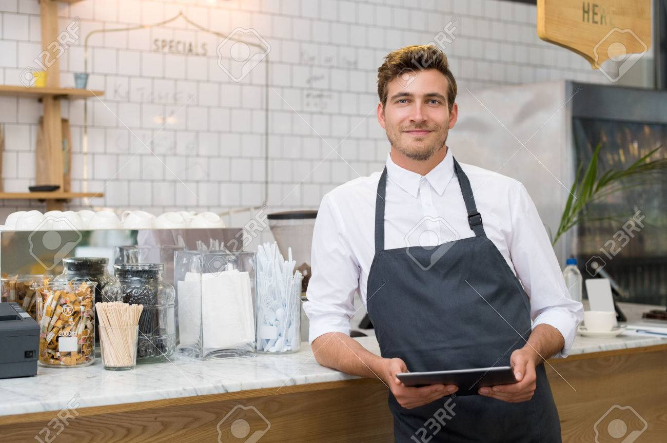 Successful small business owner holding digital tablet and looking at camera. Happy smiling waiter with apron and digital tablet leaning on counter. Portrait of young entrepreneur of coffee shop posing. Banque d'images - 59968291