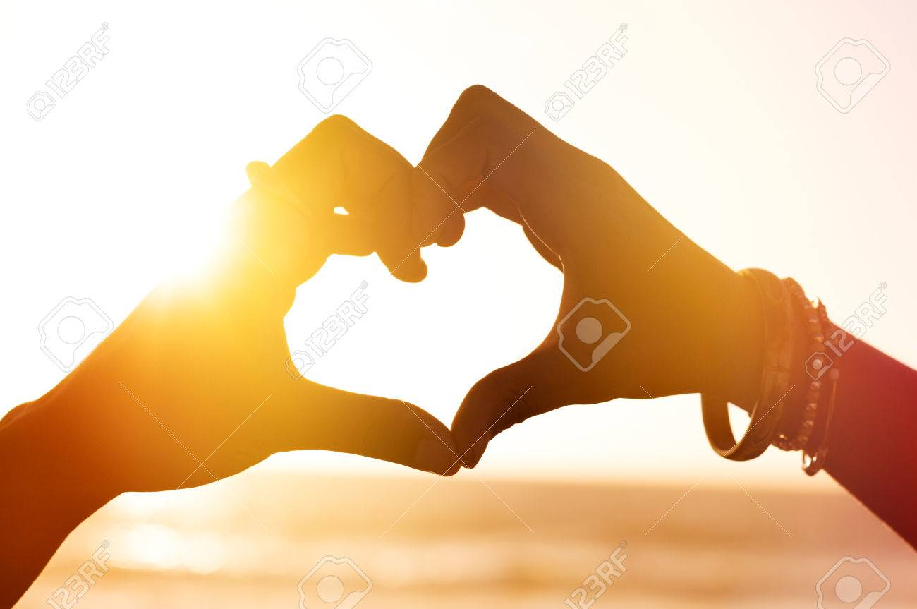 Heart shape of hands against sea during sunset. Close up of heart made of fingers at beach. Hand in shape of love heart on sunlight background, silhouette. Banque d'images - 61412523