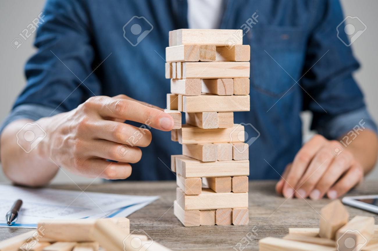 Businessman thinking about new challenge. Close up of hand of man taking a piece of building wooden bricks. Businessman trying to find a solution to problem by building with wooden bricks. Risk and strategy concept. - 64821171