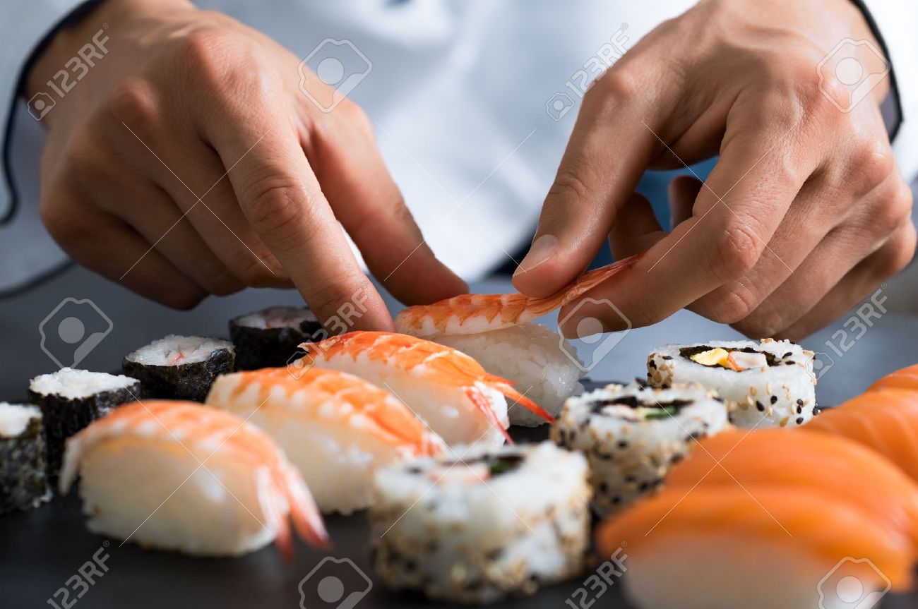 Closeup of chef hands preparing japanese food. Japanese chef making sushi at restaurant. Young chef serving traditional japanese sushi served on a black stone plate. Banque d'images - 64821179