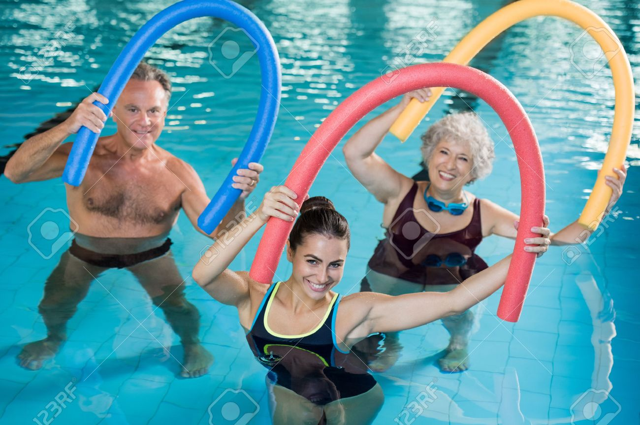Portrait of smiling people doing aqua fitness together in a swimming pool. Group of senior woman and mature man with swim noodles exercising in a swimming pool. Young trainer and senior people in aqua gym fitness class. Banque d'images - 64821184
