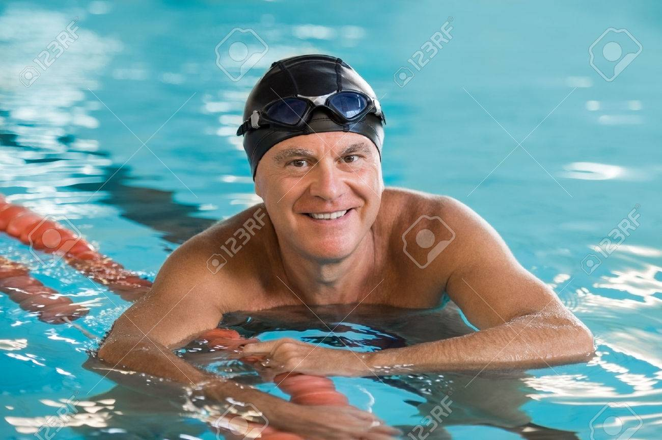 Smiling senior man standing in pool holding rope. Portrait of mature man wearing  swim cap aafdb98a2