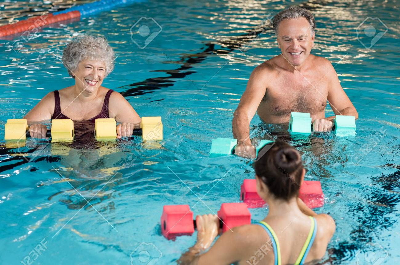 Senior couple in training session of aqua aerobics using dumbbells in swimming pool. Mature man and old woman practicing aqua fitness together. Healthy and fit senior couple enjoying their retirement in aqua aerobics training. Banque d'images - 64821187