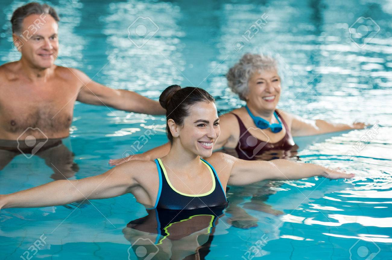 Smiling fitness class doing aqua aerobics in swimming pool. Smiling young woman with senior couple stretching arms in swimming pool while doing aqua aerobics. Fit mature man and old woman exercising in swimming pool with young woman. - 65157554