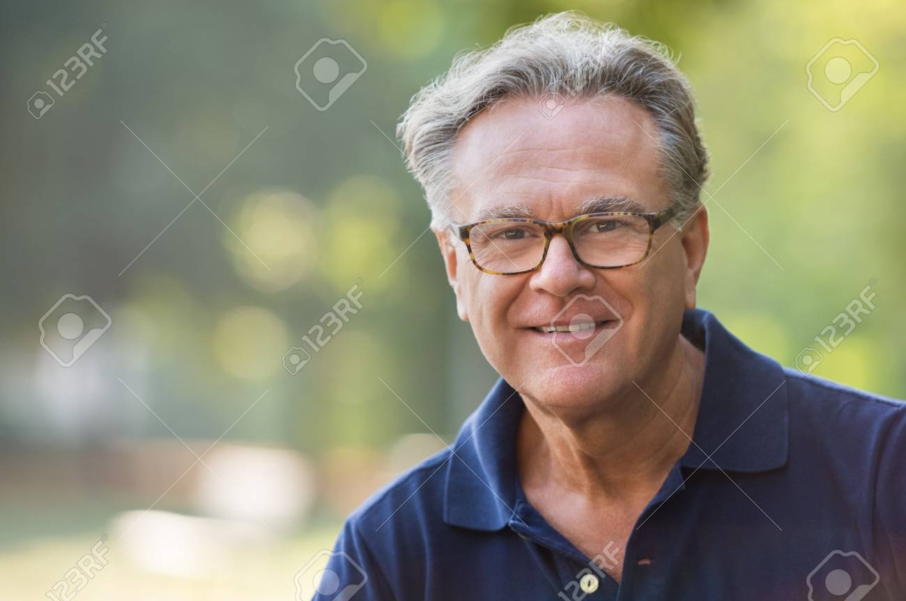 Portrait of senior man smiling and loooking at camera. Face of a happy old man wearing eyeglasses outdoor. Retired man with grey hair relaxing at park during morning. - 64821190