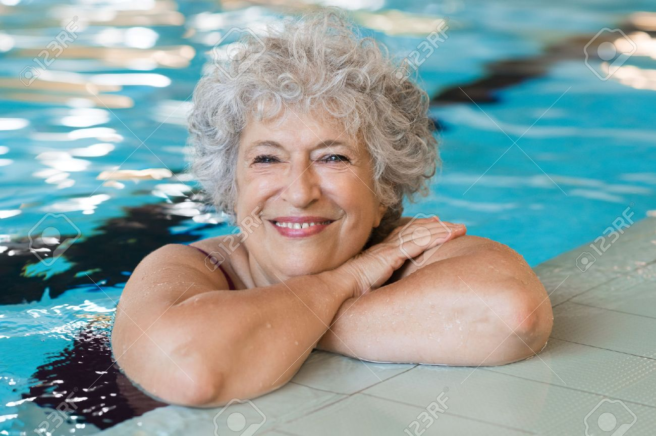 Portrait of elderly woman against the edge of a swimming pool and looking at camera. Fit and active senior woman enjoying retirement in the swimming pool. Beautiful mature woman relaxing in the swimming pool. Banque d'images - 64821194