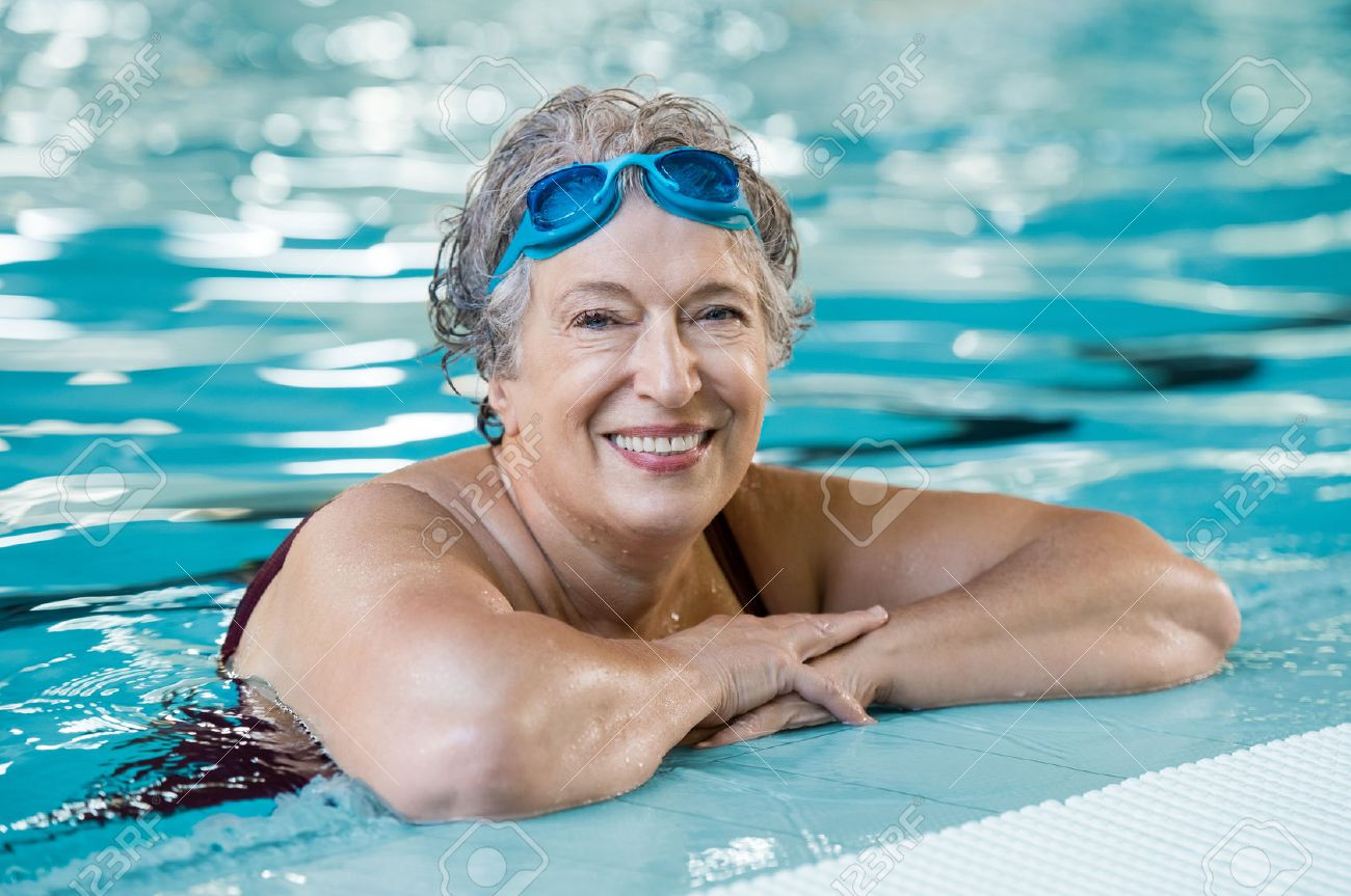 Mature woman wearing swim goggles at swimming pool. Fit active senior woman  enjoying retirement standing 45792546d