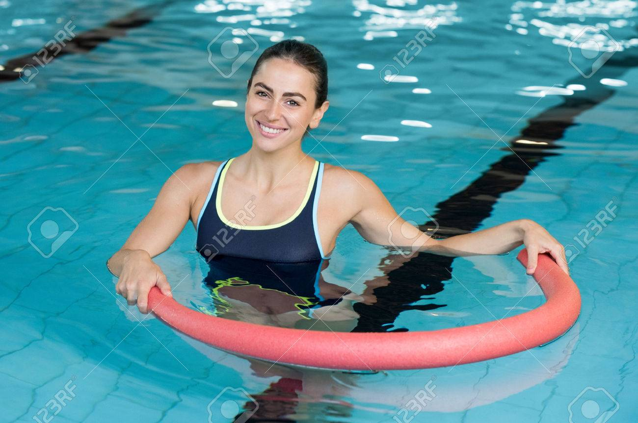 Happy smiling woman doing exercise with aqua tube in a swimming pool. Young sportive woman exercising in swimming pool with the help of a tube. Young heallthy woman doing aerobics in swimming pool. Banque d'images - 64821204