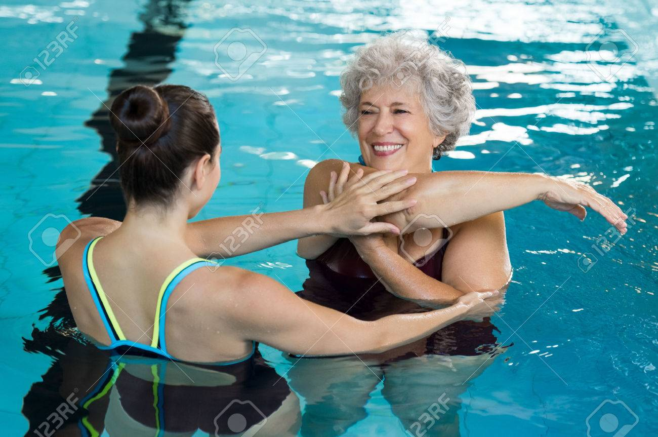 Young trainer helping senior woman in aqua aerobics. Senior retired woman staying fit by aqua aerobics in swimming pool. Happy old woman stretching in swimming pool with young trainer. Banque d'images - 65157743