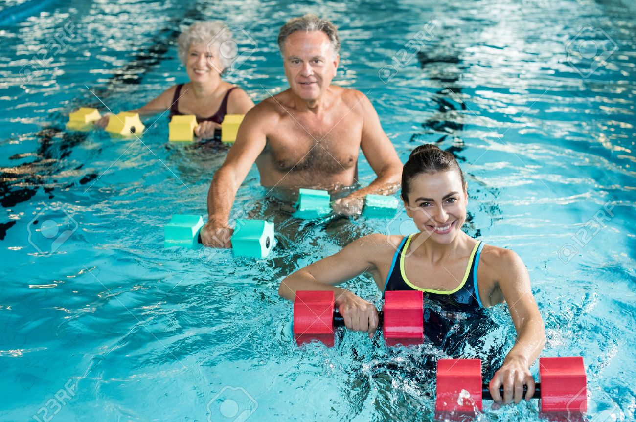 Happy active fitness mature man and senior woman doing exercise with aqua dumbbell in a swimming pool with instructor. Retired people doing aqua gym exercise with water dumbbell in swimming pool and looking at camera. Banque d'images - 64821210