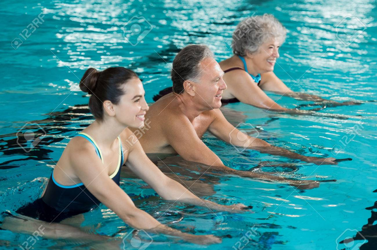 Happy smiling mature man and old woman cycling on a swimming bike in swimming pool. Happy and healthy senior people enjoying swimming with young woman. Fitness class doing aqua aerobics on exercise bikes in a swimming pool. Banque d'images - 64821182