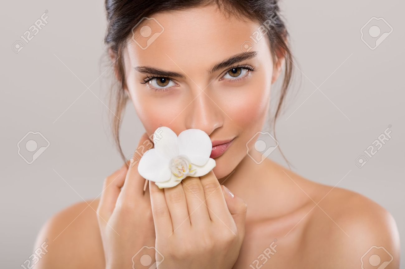 Portrait of a beautiful woman with bare shoulders holding a flower of orchid isolated on grey background. Portrait of natural beauty of young woman holding white orchid flower near face and looking at camera. Banque d'images - 65157774